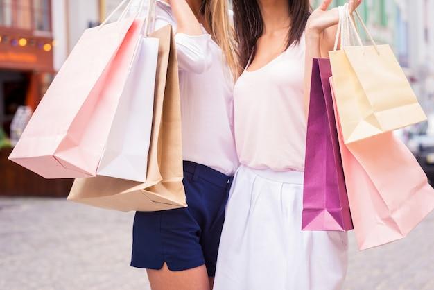 Mädchen mit einkaufstüten. nahaufnahme von zwei jungen frauen, die einkaufstüten halten, während sie im freien stehen