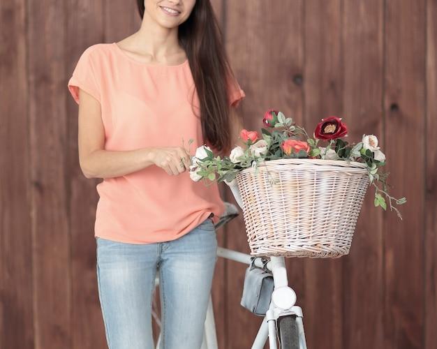 Mädchen mit fahrrad mit frühlingsblumen im korb.