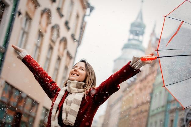 Mädchen mit fallendem aufenthalt des weißen schnees des regenschirmes auf stadtstraße