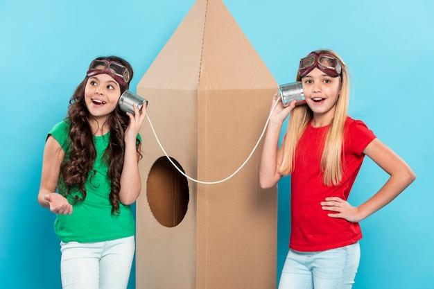 Mädchen mit fliegerbrille, die am walkie-talkie sprechen