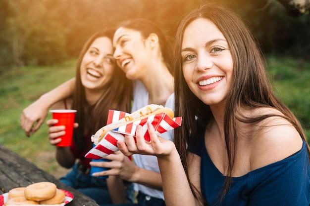 Mädchen mit freunden, die im park stillstehen