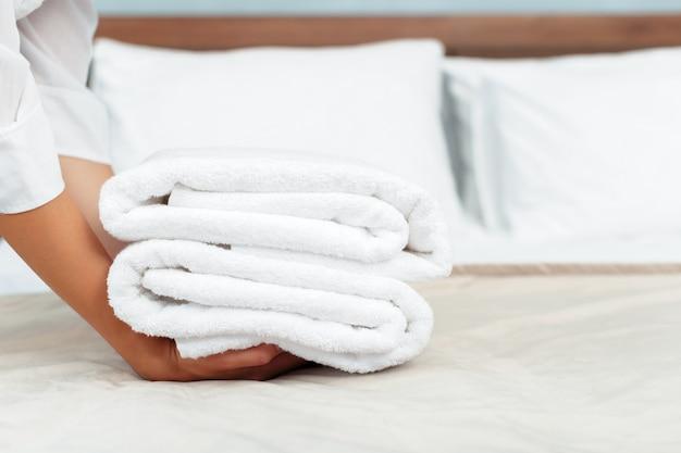 Mädchen mit frischen, sauberen handtüchern während der reinigung in einem hotelzimmer