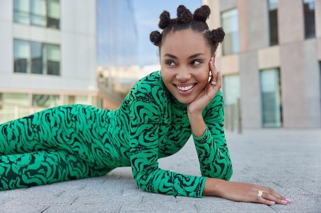 Mädchen mit gekämmten haarbrötchen helles make-up lächelt zahnig schaut weg gekleidet in grünem kostüm posiert im freien gegen modernes stadtgebäude posiert zum fotografieren