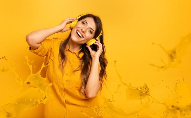 Mädchen mit gelbem headset hört musik und tänze. emotionaler und energetischer ausdruck