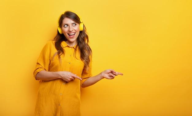 Mädchen mit gelbem headset hört musik und tänze. emotionaler und energetischer ausdruck.