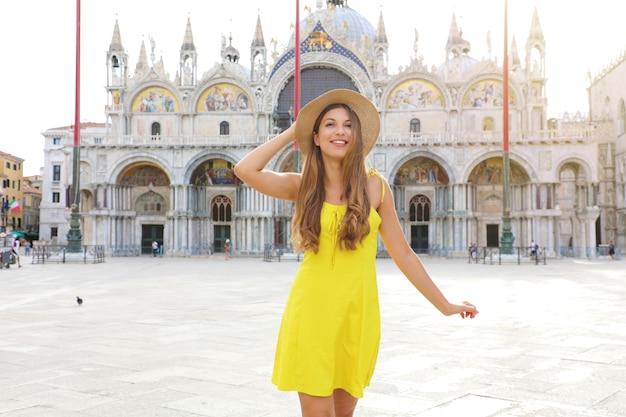 Mädchen mit gelbem kleid und hut auf dem markusplatz, venedig, italien