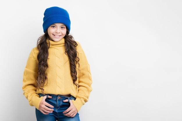 Mädchen mit gelber strickjacke und blauem hut