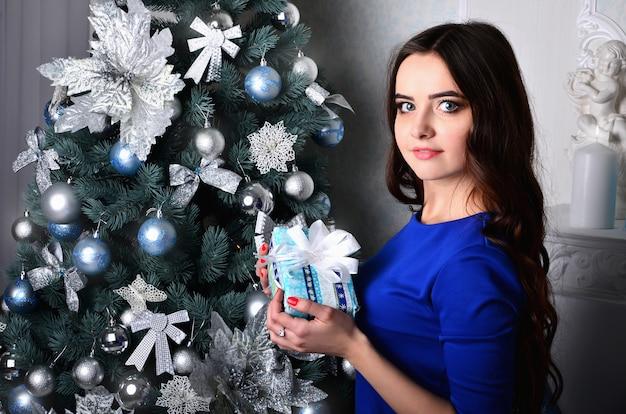 Mädchen mit geschenk nahe dem weihnachtsbaum