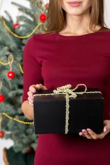 Mädchen mit geschenken auf dem hintergrund eines weihnachtsbaumes
