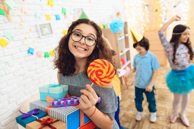 Mädchen mit geschenken hält farbigen lutscher in der hand.