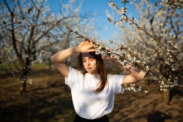 Mädchen mit geschlossenen augen posiert in der nähe der frühlingsblühenden bäume.