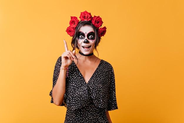 Mädchen mit gesicht für halloween gemalt hat neue lustige idee. porträt der stilvollen jungen frau mit rosen im haar.