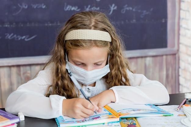 Mädchen mit gesichtsmaske zurück in der schule nach covid-quarantäne und lockdown-schulmädchen, das in übung schreibt ...