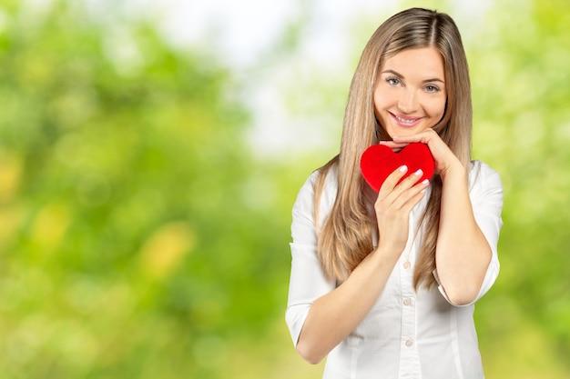 Mädchen mit glücklichem romantischem gesicht hält stofftierherz mit den händen