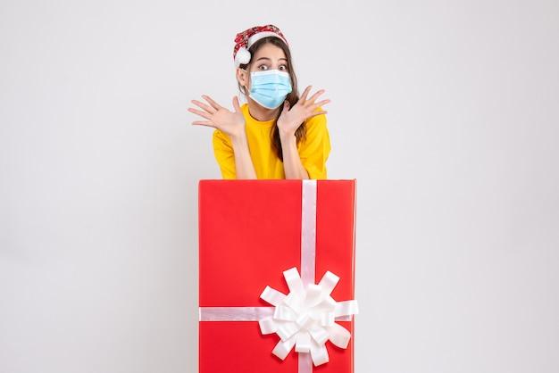 Mädchen mit großen augen und weihnachtsmütze, das die hände öffnet, die hinter großem weihnachtsgeschenk auf weiß stehen