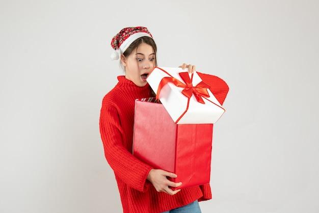 Mädchen mit großen augen und weihnachtsmütze, das ihr weihnachtsgeschenk auf weiß öffnet