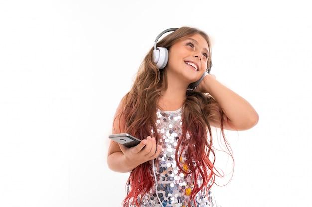 Mädchen mit großen weißen kopfhörern, die musik hören, ihren linken kopfhörer berühren und schwarzes smartphone isoliert halten