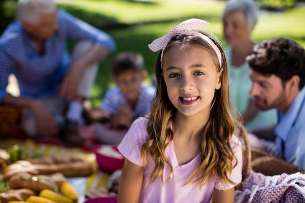 Mädchen mit haarband und familie, die das picknick im hintergrund genießen
