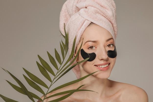 Mädchen mit handtuch auf dem kopf mit gesichtsmaske