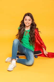 Mädchen mit heldenkostüm, das auf skateboard sitzt