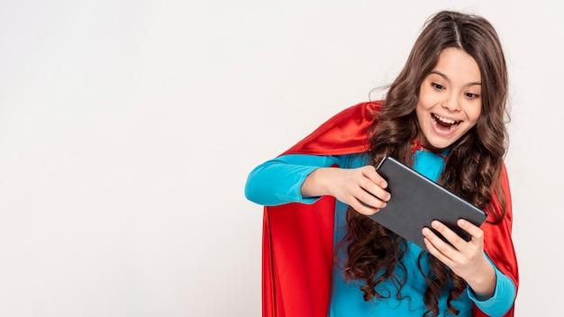 Mädchen mit heldenkostüm, das auf tablette spielt