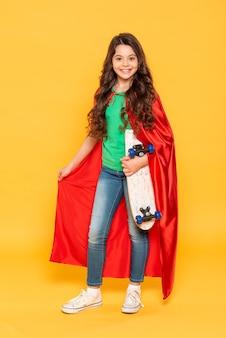 Mädchen mit heldenkostüm, das skateboard hält