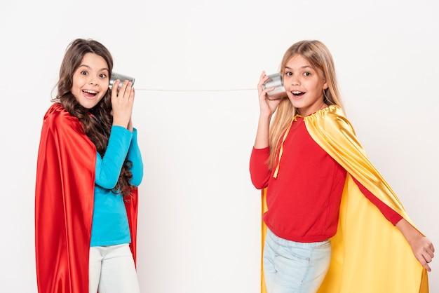 Mädchen mit heldenkostüm und walkie talkie