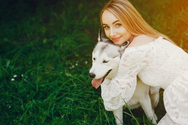 Mädchen mit hellen haaren in weißen kleid gekleidet spielt mit ihrem hund