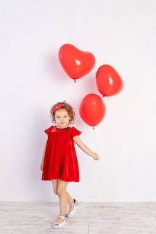 Mädchen mit herzförmigen luftballons in einem roten kleid auf einem weißen hintergrund, das konzept der liebe und des valentinstags