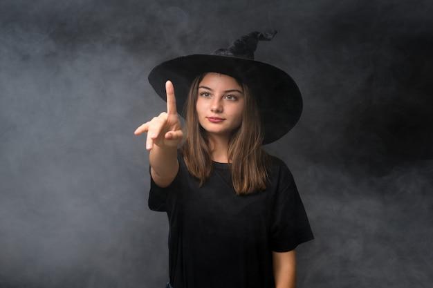 Mädchen mit hexenkostüm für halloween-partys über der lokalisierten dunklen wand, die auf transparentem schirm sich berührt