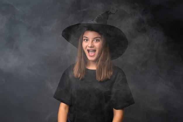 Mädchen mit hexenkostüm für halloween-partys über lokalisierter dunkler wand mit überraschungsgesichtsausdruck