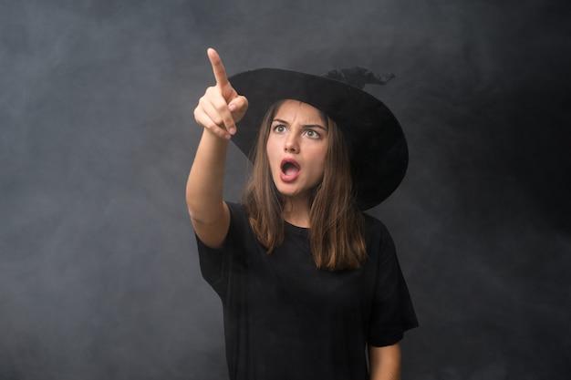 Mädchen mit hexenkostüm für halloween-partys über lokalisierter dunkler wand weg zeigend