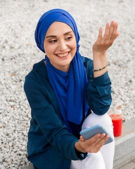 Mädchen mit hijab, der am telefon spricht