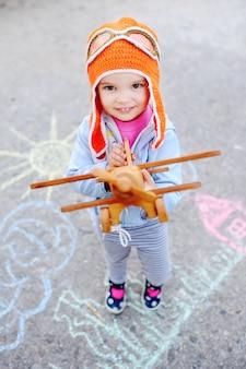 Mädchen mit hölzernem spielzeugflugzeug und orange versuchskappe