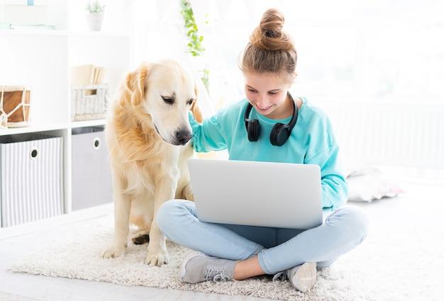 Mädchen mit hübschem hund, der im hellen raum am laptop arbeitet