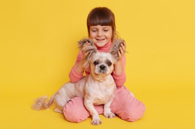 Mädchen mit hund, der zusammen spielt, hebt die ohren des welpen und lacht auf gelb