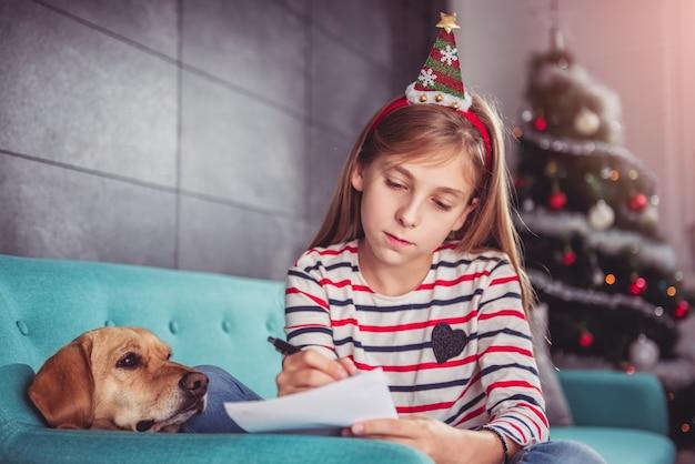 Mädchen mit hundeschreibenswunschliste auf sofa