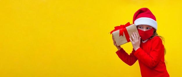 Mädchen mit hut santa in seinen händen hält geschenk für weihnachten neujahr hört zu, was dort banner liegt