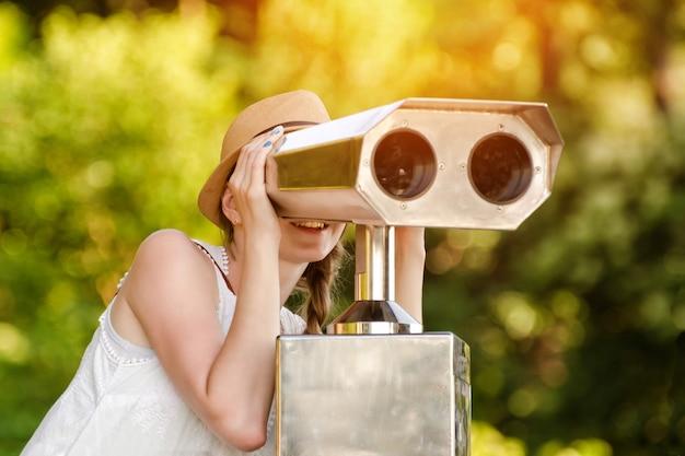 Mädchen mit hut schaut in das große fernglas.