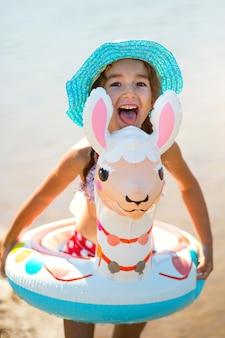 Mädchen mit hut steht es am ufer mit aufblasbarem kreis in form eines lamas. aufblasbares alpaka für ein kind. meer mit sandigem grund. strandurlaub, schwimmen, bräunen, sonnencreme.