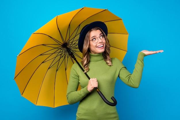 Mädchen mit hut und brille hält regenschirm