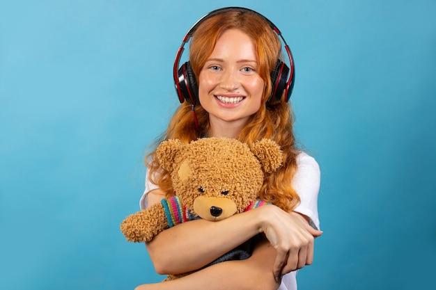 Mädchen mit ihrem geliebten bären. hört musik mit kopfhörern, posiert und lächelt. foto auf einer blauen wand.