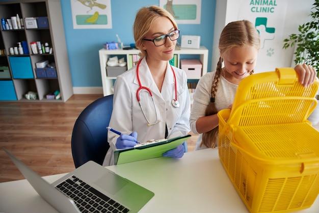 Mädchen mit ihrem haustier beim tierarzt