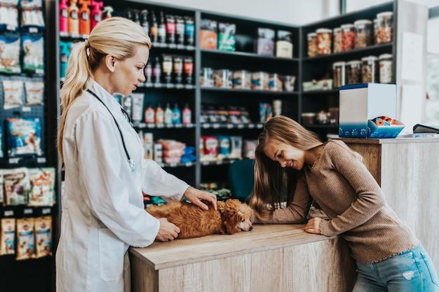 Mädchen mit ihrem pudelwelpen beim tierarzt