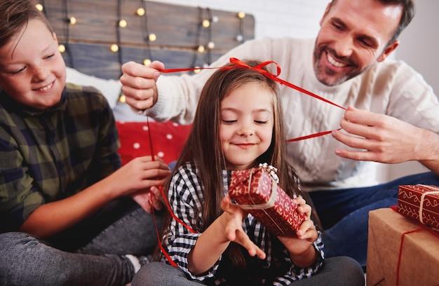 Mädchen mit ihrer familie, die weihnachtsgeschenk öffnet