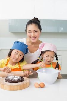 Mädchen mit ihrer mutter, die plätzchen in der küche vorbereitet