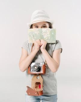 Mädchen mit kamera und karte im studio