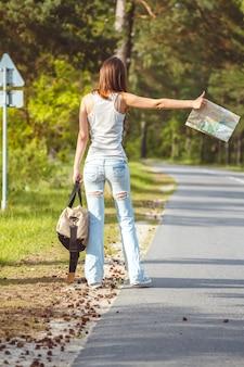 Mädchen mit karte und tasche in der hand, die auf einem straßenrand geht