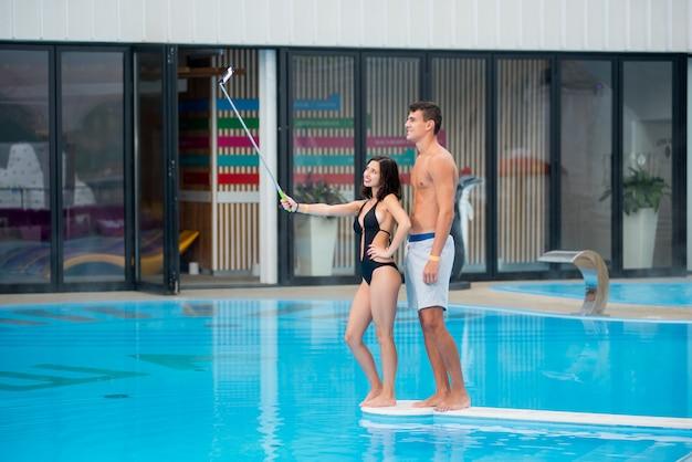 Mädchen mit kerl nahe dem swimmingpool, der selfie foto macht