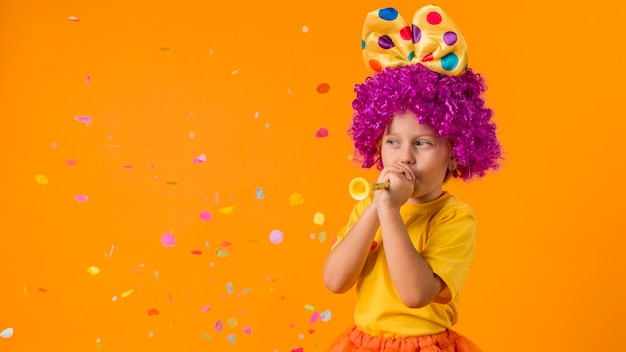 Mädchen mit konfetti und clownkostüm
